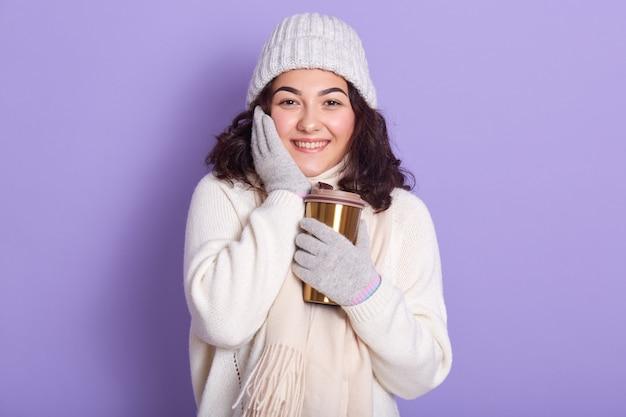 Immagine di giovane dolce modello sveglio che tocca il suo cheeck con la mano, tenendo la tazza termica in una mano