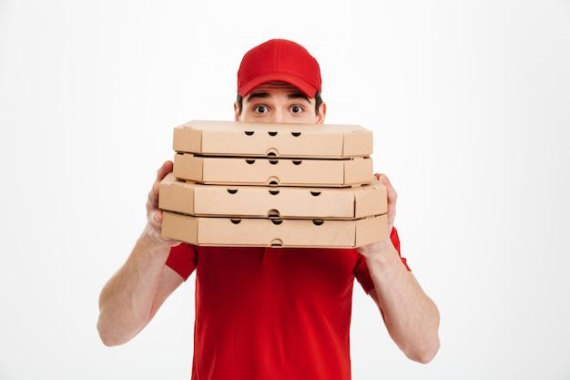 Immagine di giovane fattorino in maglietta rossa e cappuccio che copre il viso con una pila di scatole per pizza, isolato su uno spazio bianco