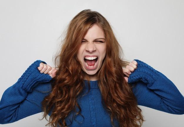 Immagine di giovane femmina insoddisfatta infuriata che fa smorfie e che fa gesto arrabbiato.
