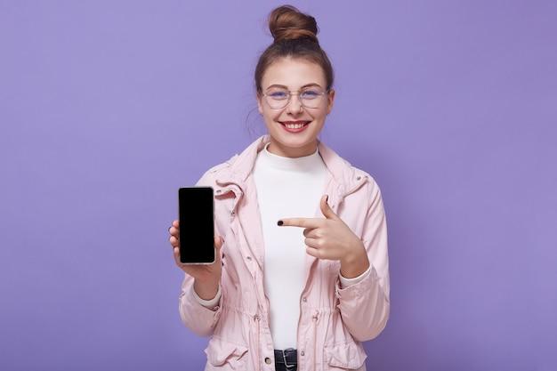 Immagine di giovane femmina positiva allegra che indossa i vestiti alla moda, tenendo smartphone in una mano, mostrando direzione con l'indice, sorridendo sinceramente, presentando il nuovo modello del dispositivo. concetto di tecnologia.