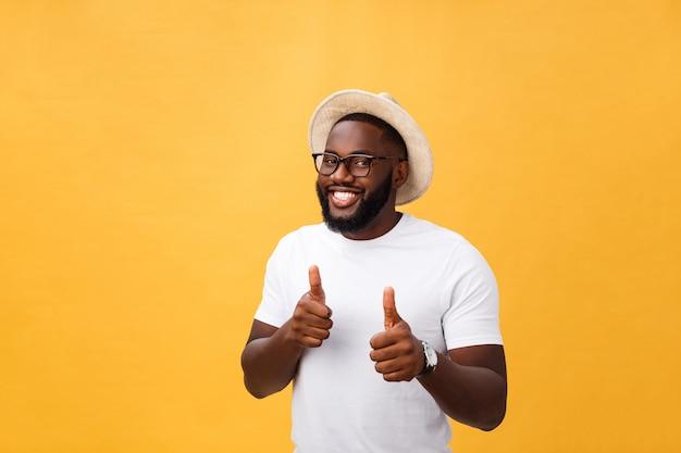 Immagine di giovane uomo africano allegro che sta e che posa sopra fondo giallo con i pollici su