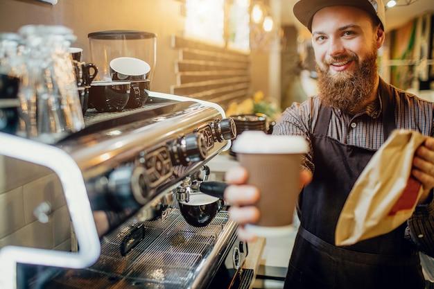 Immagine di giovane uomo barbuto che tiene tazza di caffè e borsa con alimento