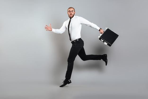 Immagine di giovane uomo confuso in bicchieri e tailleur scappando con valigetta piena di banconote da un dollaro in mano, isolato su muro grigio