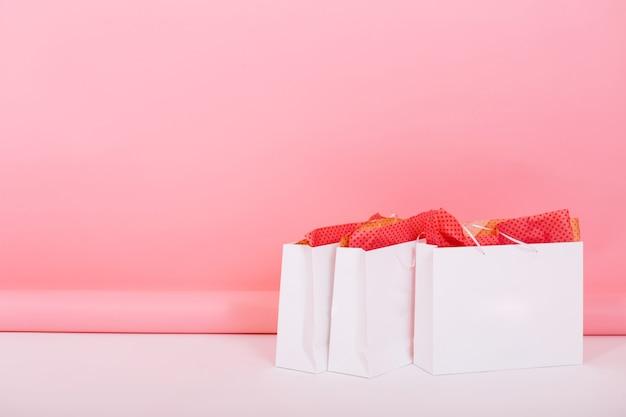 Immagine di grandi sacchetti di carta dal negozio con confezioni regalo ornamento all'interno in piedi sul pavimento su sfondo rosa. qualcuno ha preparato regali romantici per l'anniversario di matrimonio lasciandoli in camera
