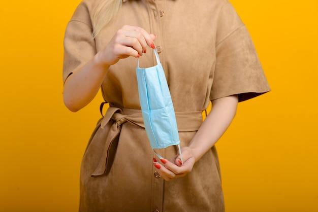 Immagine di mani femminili con maschera blu contaminazione da epidemie di covid 19