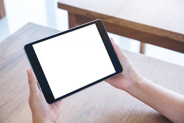 Immagine di mockup delle mani che tengono e utilizzando tablet pc nero