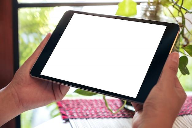 Immagine di mockup delle mani che tengono tablet pc nero con schermo desktop bianco vuoto