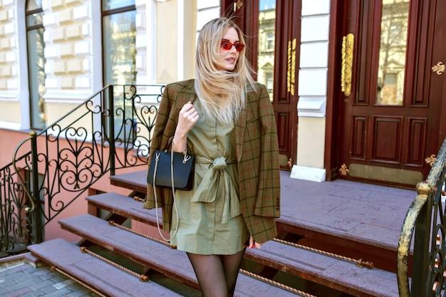 Immagine di moda all'aperto della splendida modella bionda in posa per la strada di parigi, vestito alla moda con giacca moderna oversize, mezza stagione autunnale primavera, colori dai toni caldi.