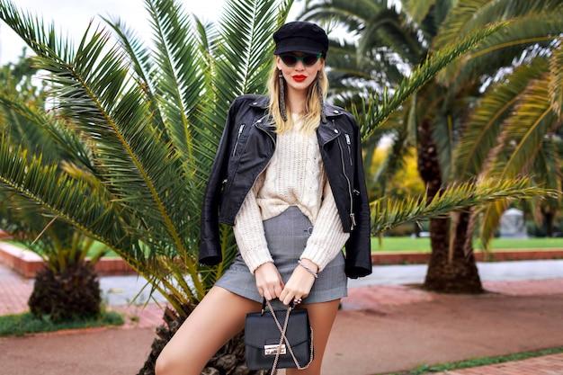 Immagine di moda all'aperto di donna elegante ed elegante in posa nelle strade di barcellona vicino a palme, con indosso giacca di pelle, berretto, occhiali da sole retrò, borsa piccola, maglione bianco accogliente e gioielli alla moda, minigonna.