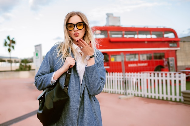 Immagine di moda all'aperto di giovane donna alla moda che propone alla via di londra, vestito elegante di affari casuali, invio di bacio e guardando sulla fotocamera, tempo di mezza stagione autunno primavera, colori tonica.