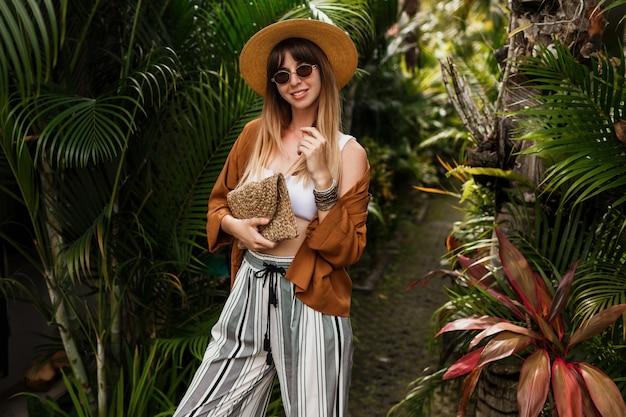 Immagine di moda di donna graziosa sexy in cappello di paglia in posa su foglie di palma tropicale