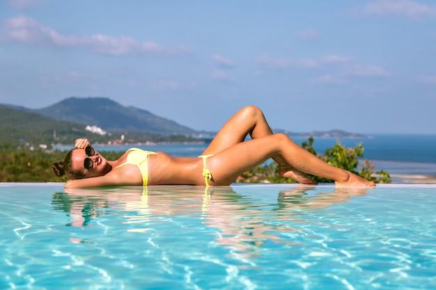 Immagine di moda di splendida donna sexy con corpo slim fit rilassante vicino alla piscina a sfioro, su un'isola tropicale esotica, giornate calde, bikini, vita di lusso, atmosfera da vacanza di viaggio.
