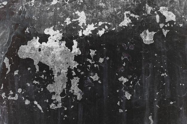 Immagine di sfondo di vecchia parete ruvida con il primo piano nero incrinato della pittura.