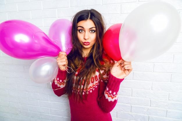 Immagine di stile di vita al coperto di divertente bella ragazza mora con trucco luminoso e capelli lunghi, che indossa un maglione alla moda e che tiene palloncini rosa.