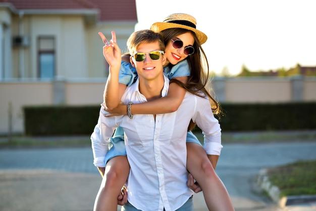 Immagine di stile di vita all'aperto di coppia felice innamorata che si diverte e impazzisce insieme, baci e abbracci, appuntamento romantico, luce solare serale, strada, viaggi, ragazzi eleganti alla moda, bellissimi amanti.