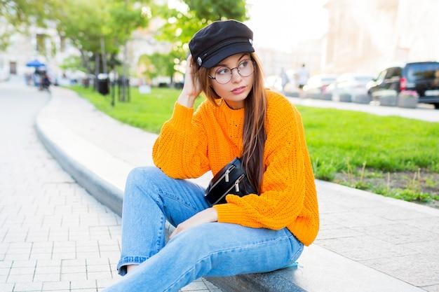 Immagine di stile di vita all'aperto di romantica donna sognante seduto sul marciapiede e godersi la serata.
