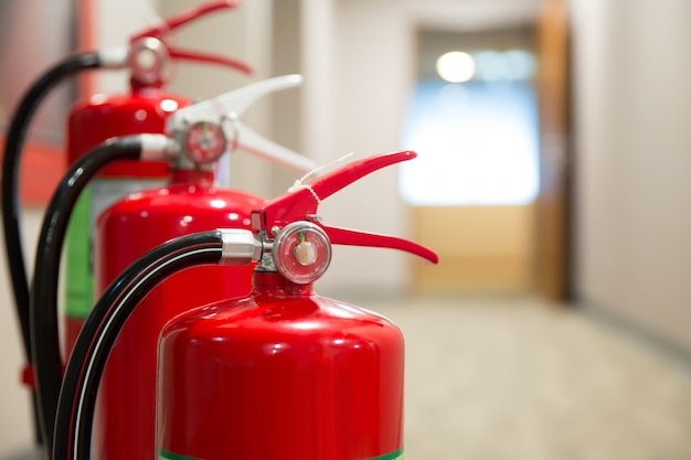 Immagine di un estintore con manichetta antincendio sul lato destro preparare per la sicurezza e la prevenzione degli incendi.