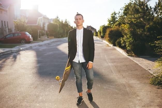 Immagine di un uomo con longboard andando sulla strada