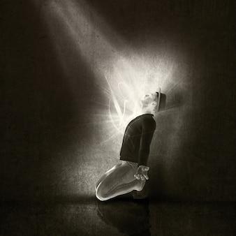 Immagine di un uomo in ginocchio in adorazione di un raggio di luce in un interno grunge