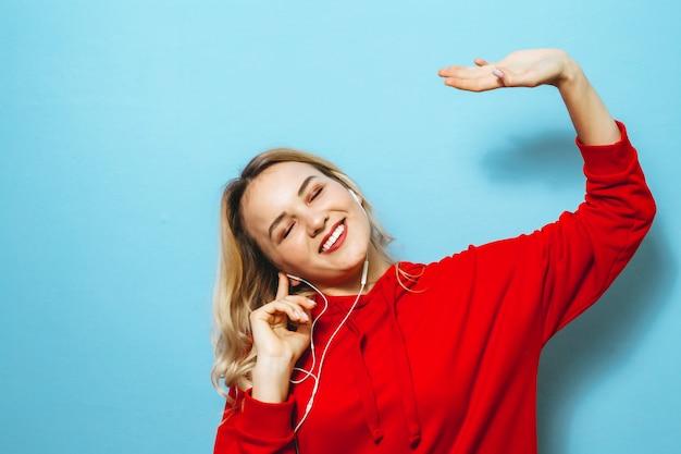 Immagine di una bella ragazza bionda eccitata ascoltando musica in cuffia e ballando sul muro blu