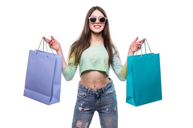 Immagine di una giovane donna scioccata in abito estivo bianco che indossa occhiali da sole in posa con le borse della spesa.