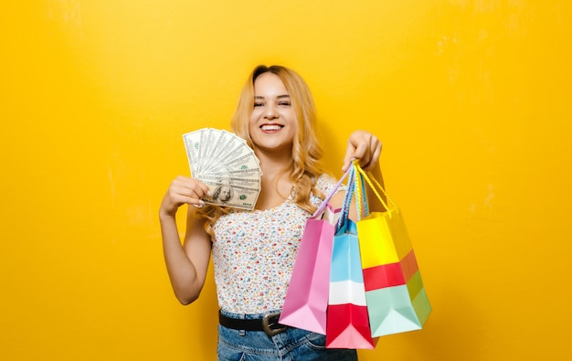 Immagine di una giovane ragazza bionda eccitata in possesso di banconote e shopping bag su sfondo giallo