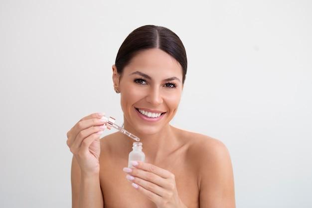 Immagine di una posa sorridente della giovane donna isolata sopra fondo bianco siero di goccia dell'olio della tenuta. la giovane donna usa il siero per il viso.