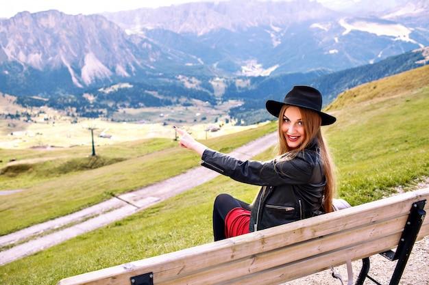 Immagine di viaggio all'aperto della donna alla moda che si siede in panchina al resort di montagna, che mostra con la sua mano su una vista incredibile sulle montagne dell'alpe, viaggio di lusso.