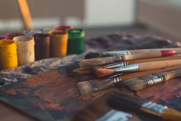 Immagine di vista di angolo di vecchia tavolozza con le pitture ad olio e l'insieme di gouache. luogo di lavoro pulito del pittore pronto per il disegno.
