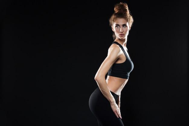 Immagine di vista laterale di giovane posa di signora di sport.