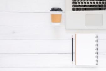 Immagine di vista superiore del notebook aperto con pagine bianche e laptop sul tavolo di legno