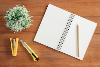 Immagine di vista superiore del notebook aperto con pagine bianche sul tavolo di legno