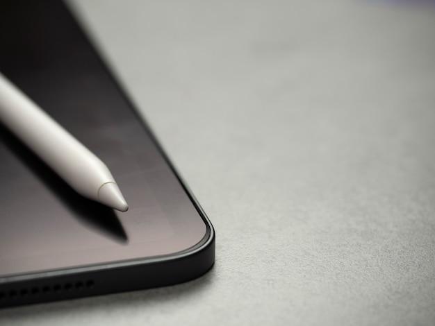 Immagine di vista superiore della penna dello stilo sulla nuova compressa lussuosa in bianco nera con lo spazio della copia