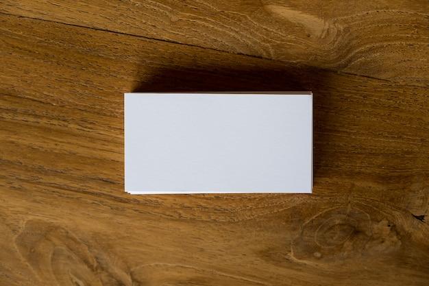 Immagine di vista superiore della pila di biglietti da visita sul fondo della tavola in legno