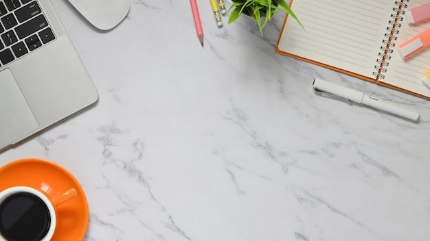Immagine di vista superiore della tazza di caffè in ceramica, pianta in vaso, nota, penna e pennarelli che uniscono sulla tabella di marmo di struttura. concetto di posto di lavoro creativo.
