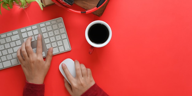 Immagine di vista superiore delle mani che digitano sulla tastiera wireless e utilizzando un mouse wireless sullo scrittorio funzionante rosso circondato dalla tazza di caffè, dalla cuffia senza fili, dai vecchi libri e dalla pianta in vaso. concetto di spazio di lavoro ordinato.
