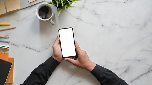 Immagine di vista superiore delle mani dell'uomo d'affari che tengono uno smartphone nero potato con lo schermo in bianco bianco sulla tavola di marmo di struttura. tazza da caffè, pianta in vaso, matite, taccuino e diario.