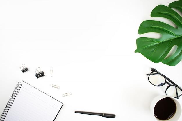 Immagine di vista superiore su un'area di lavoro bianca della tabella con il computer portatile, la foglia di palma, il taccuino e gli accessori. vista piana, vista dall'alto.
