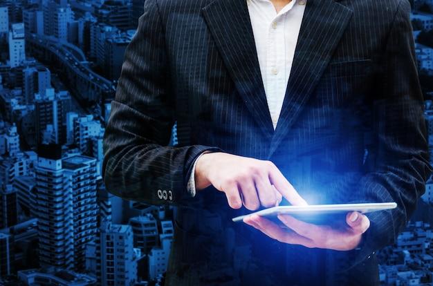 Immagine doppia esposizione del giovane investitore o uomo d'affari intelligente utilizzando la tavoletta mobile digitale con sfondo di paesaggio urbano, trading, borsa, tecnologia internet, investimenti e concetto di business globale