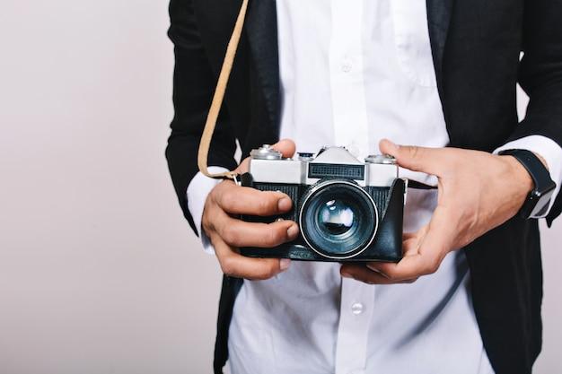 Immagine elegante della fotocamera retrò nelle mani del bel ragazzo in tuta. tempo libero, giornalista, fotografia, hobby, divertimento.