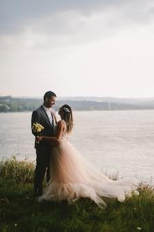 Immagine emotiva della coppia appena sposata che sta nel campo e che si guarda con amore. fiume sullo sfondo.