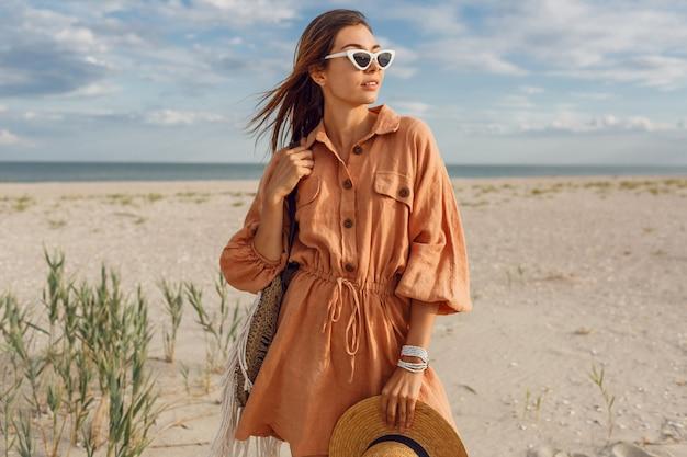 Immagine estiva di bella donna castana in abito di lino alla moda, che tiene il sacchetto di paglia. ragazza abbastanza magra che gode dei fine settimana vicino all'oceano.