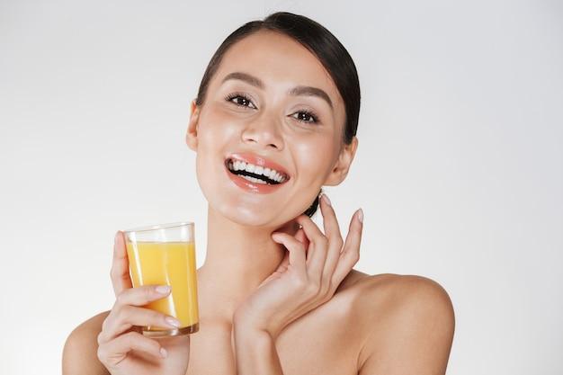 Immagine felice di signora mezza nuda che sorride e che beve il succo d'arancia appena spremuto da vetro trasparente, isolata sopra la parete bianca