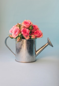 Immagine floreale minimale con mini annaffiatoio e rose rosa contro il blu pastello