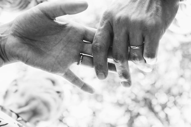 Immagine in bianco e nero delle mani delle persone appena sposate che si tengono tenero