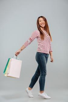 Immagine integrale della donna asiatica felice nella camminata del maglione