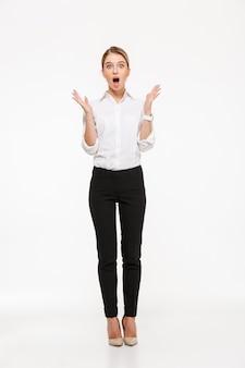 Immagine integrale della donna bionda colpita di affari che si tiene per mano vicino alla testa e con la bocca aperta sopra la parete bianca