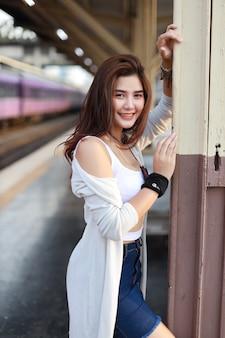 Immagine integrale di giovane donna asiatica, capelli lunghi in vestito bianco che sta e che esamina macchina fotografica mentre aspettando nella stazione ferroviaria con il fronte di bellezza