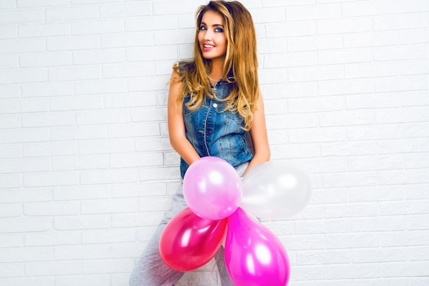 Immagine interna sulla giovane donna bionda alla moda hipster, giocando con palloncini rosa, pronta per la festa.