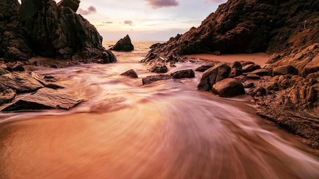 Immagine lunga di esposizione del cielo drammatico e del paesaggio marino dell'onda con roccia nel fondo di paesaggio di tramonto